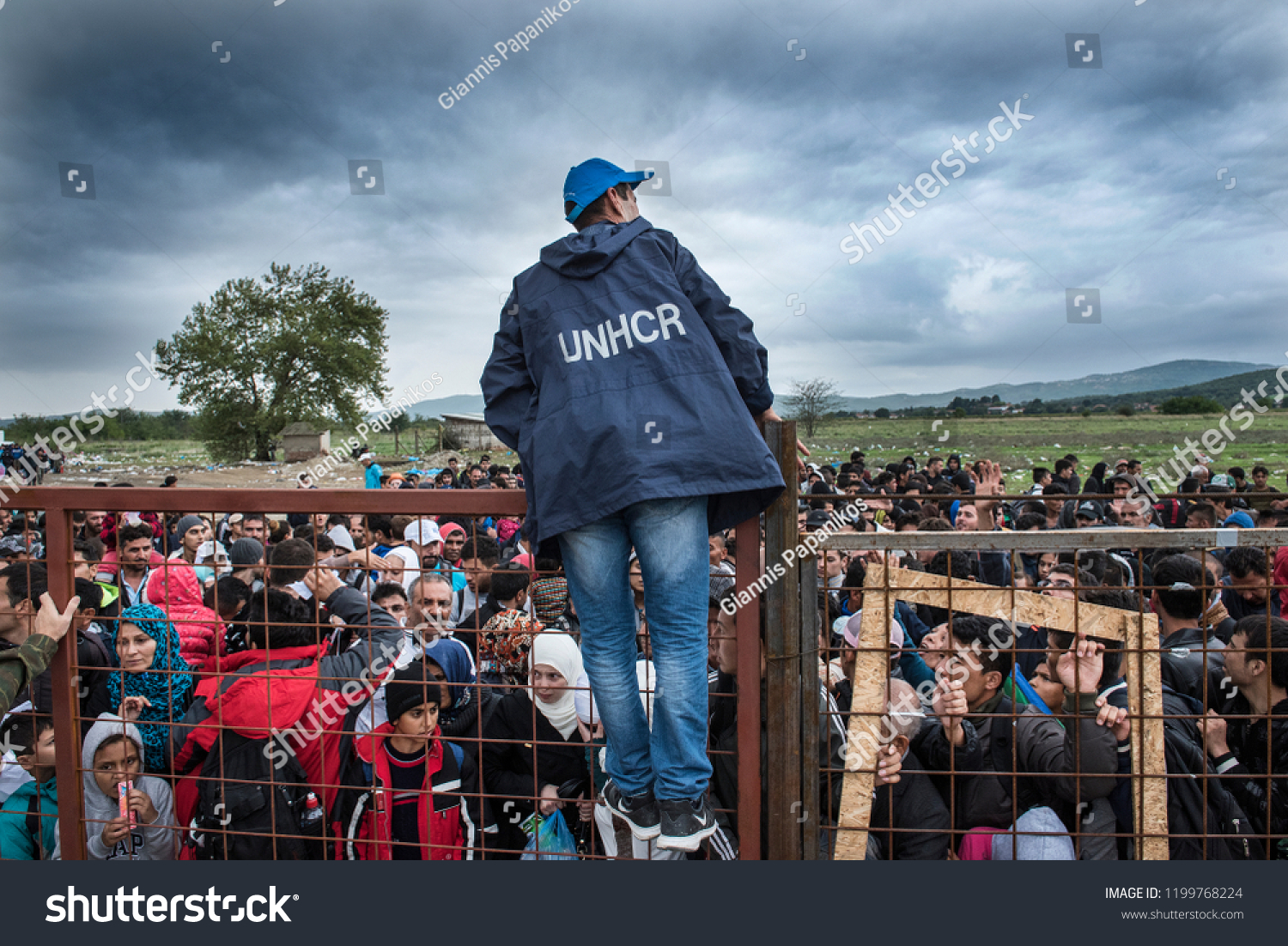 stock photo gevjelija macedonia september a unhcr employee talks to refugees as they wait during a 1199768224